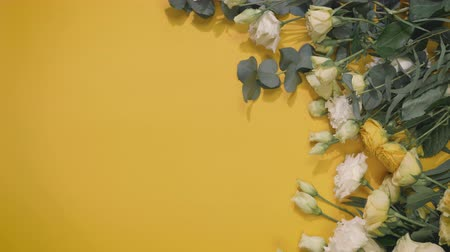 flowers bunch on yellow background with copy space for text, florist deploys paper for still life, vertical screen