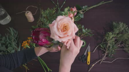 working day in floristic studio store salon, professional florist woman prepares flowers to bunch, closeup hands, floral business concept