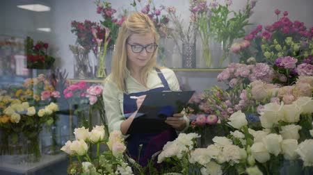 portrait of a beautiful smiling girl professional florist owner of a small business working in a flower shop checks quality of flowers, a successful startup