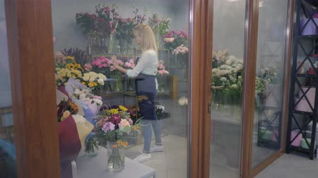 young professional female florist works in a greenhouse, checks flowering for making a bouquet for delivery, flower shop