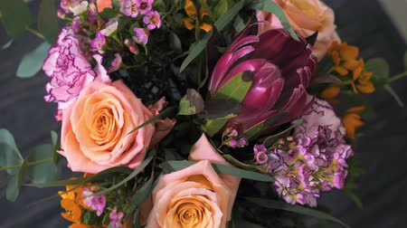floristry, a modern bouquet of beautiful flowers, slowly rotated on a dark background, close-up