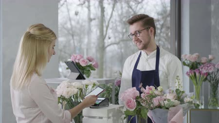 successful startup, young man representative gender equality at work sells bouquet of fresh beautiful flowers to happy female customer who pays purchase by contactless payment with smartphone
