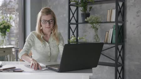 empregador : young happy calm woman holds hands behind head feeling relieved relaxes and sits at home office with beautiful fresh flowers interior desk with laptop, female student enjoys successfully completed work, plants interior