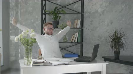 joyful man is holding hands behind head while sitting on chair near table with computer in an office with modern floral interior on background of fresh bouquets of flowers, happy male employee is enjoying rest at work, without stress Stock Footage