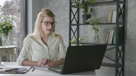 empregador : successful business, a young businesswoman entrepreneur uses modern technology for video communication, a woman communicates with partners using online communications in floral interior Stock Footage