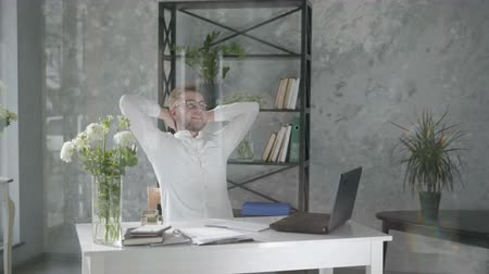 happy male businessman small business owner works in an office with a modern floral interior on the background of fresh bouquets of flowers at computer, satisfied with successful work throws hands behind his head and enjoys his vacation, plants interior