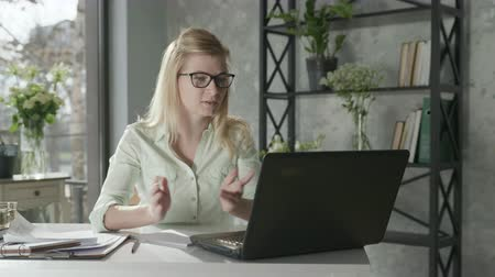empregador : young female entrepreneur discussion video calls with business partner sitting at table with laptop in office next to beautiful bouquet of flowers, communicating online concept