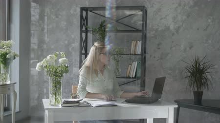 young girl works at a computer, happy business woman in modern office with floral interior at laptop checks online bookkeeping background of fresh flowers, small business