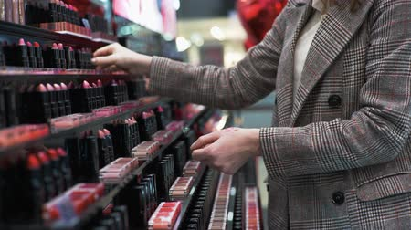 装飾品 : girl chooses makeup cosmetics, tests lipstick while shopping at the cosmetics store, close-up