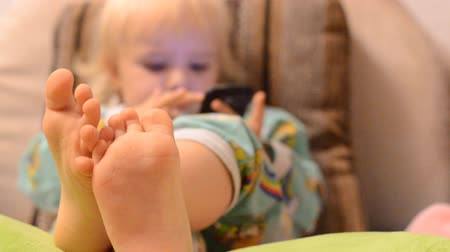 telefones : Baby playing with phone, focus on the legs