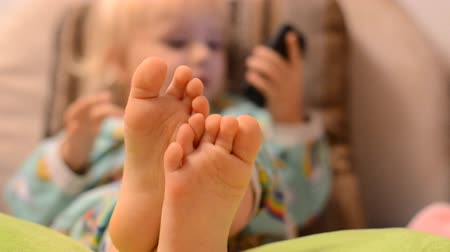dialog : Baby playing with phone, focus on the legs