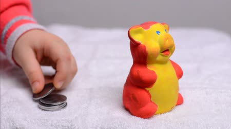 экономика : Little Baby Putting Coins into Moneybox