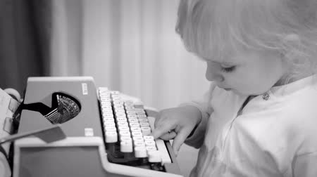 tipo : Cute Baby Girl Writing a Book on a Vintage Typewriter, Black and White Vídeos