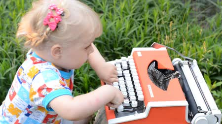 tipo : Retro Typewriter Machine in use. Little Girl Writer Printing in a Garden.