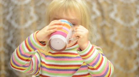 içme : Little girl drinks  emotionally and  sign thumb up