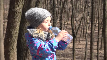experiência : Little girl drinks water from a bottle. 4K UltraHD, UHD