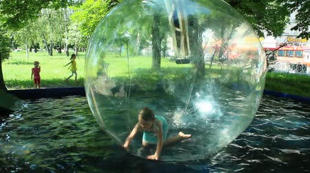 water jet : little girl playing in the transparent sphere