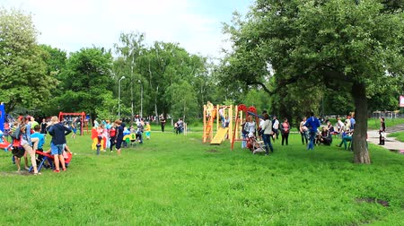 жизнь : many children playing on the playground with their parents