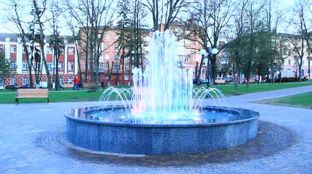 Colored fountains in city park. Colorful jets of water. Lifestyle concept. People walking in city park with fountains