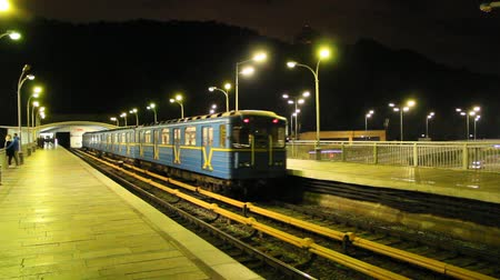 Elektrischer Zug, der Station in der U-Bahn am Abend verlässt. Zug verlässt die Metrostation. U-Bahn ab Metrostation Hydropark in Kiew. Passagierplattform in der U-Bahn