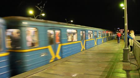 Electric train leaving station in subway in evening. Train leaving metro station. Underground train departing from Hydropark metro station in Kyiv. Passenger platform in subway