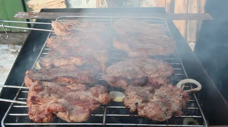 Steak grilling on fire. Process of cooking meat. Steak on barbecue. Pieces of grilled meat on grill. Cooking of pork. Barbecue lunch outdoors. Cooking meaty food on fire