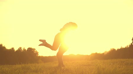 genç çift : Romantic young couple silhouette. Woman is running to her man, they hug and spin around on a sunset with sun shining bright behind them on a horizon. Slow motion filmed at 250 fps.
