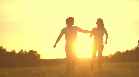 genç çift : Romantic young couple silhouette are holding hands and running forward on a sunset with sun shining bright behind them on a horizon. Slow motion filmed at 250 fps. Stok Video