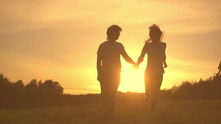 sylwetka : Romantic young couple silhouette are holding hands and running forward on a sunset with sun shining bright behind them on a horizon. Slow motion filmed at 250 fps. Wideo