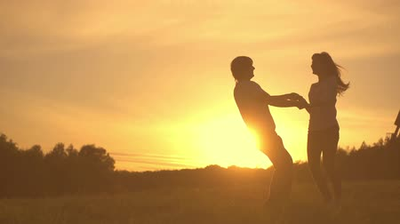 романтика : Romantic young couple silhouette are dancing, holding hands and spinning around on a sunset with sun shining bright behind them on a horizon. Slow motion filmed at 250 fps. Стоковые видеозаписи