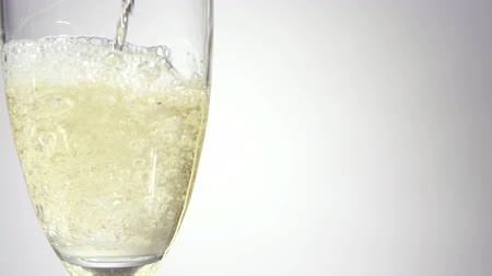 szampan : Champagne is pouring in a classic glass on a grey background. Slow motion. Filmed at 250 fps Wideo