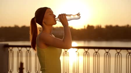 copo : Beautiful athletic woman is drinking pure water from the bottle refreshing herself after running. Slow motion filmed on 250 fps.