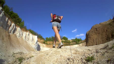 wspinaczka górska : Hiking woman in Grand Canyon. Strong happy woman tourist is reaching the point of her journey and standing with hands up in sunny canyon.  Slow motion filmed at 250 fps.