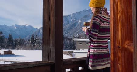 sexualita : Woman in the morning. Young smiling woman enjoying sunny morning in the Alps mountains drinking tea or coffee on a balcony in the chalet house with a mountain view. 4K UHD, slow motion