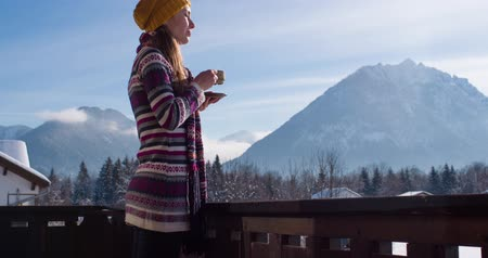 lento : Woman in the morning. Young smiling woman enjoying sunny morning in the Alps mountains drinking tea or coffee on a balcony in the chalet house with a mountain view. 4K UHD, slow motion