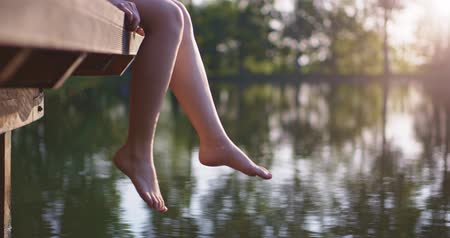 platform edge : Woman relaxes by the lake sitting on the edge of a wooden jetty , swing ones feet near the water surface. Sunny joyful summer morning concept. 4K, DCi resolution, slow motion.