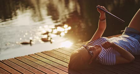 comprimido : Woman using digital tablet outdoors, relaxing on a wooden jetty near the lake with sunny background, lens flare.  4K, DCi resolution, slow motion.