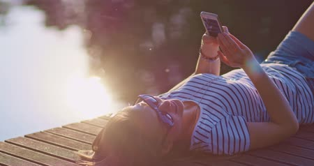 atracação : Woman using smartphone outdoors, smiling and relaxing on a wooden jetty near the lake with sunny backlit background, lens flare. Stock Footage