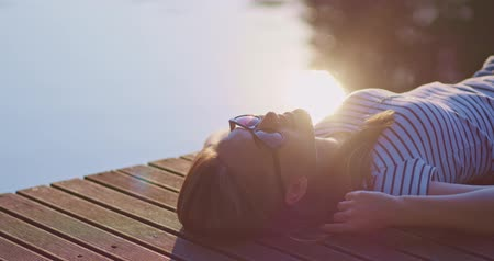 wood : Woman relaxing and smiling on a wooden jetty near the lake with morning sunny backlit background, lens flare. 4K, DCi resolution, slow motion.