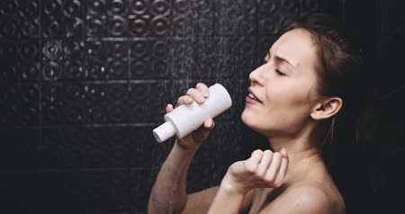 şampuan : Woman taking shower in slow motion 120fps.Young happy woman taking a shower and singing in a shampoo bottle as a microphone. Fun in daily life.