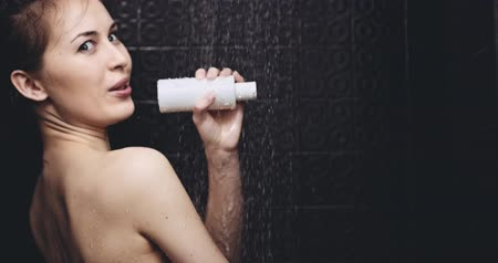 şampuan : Woman taking shower in slow motion 120fps. Young happy woman taking a shower and singing in a shampoo bottle as a microphone. Fun in daily life. Stok Video