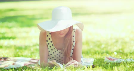 ležící : Woman reading a book in the park outdoors. Slow motion. Beautiful romantic lady in white hat laying on the green grass lawn and looking through the novel pages and daydreaming on a sunny day. 4K, DCi. Dostupné videozáznamy
