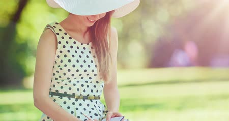 írás : Woman writing in a diary in the green park outdoors, Slow motion. Beautiful lady in a white hat making notes in her notebook, sitting on a lawn, smiling and enjoying nature in a summer garden. 4K.