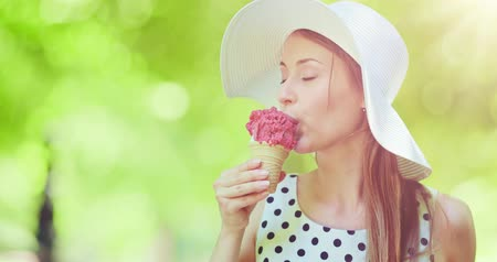 dondurma : Beautiful woman eating ice cream in the park. Slow motion, portrait. Stylish young attractive woman in white hat enjoying tasty ice cream and nature in the green sunny summer outdoors. 4K, DCi. Stok Video