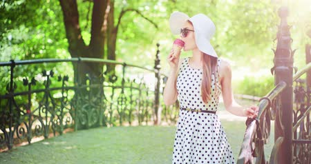 конусы : Beautiful woman eating ice cream in the park. Slow motion. Stylish young attractive woman in white hat and dress enjoying tasty ice cream and nature in the green sunny summer outdoors. 4K, DCi.