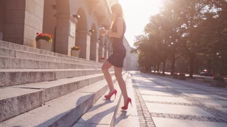 vysoký : Sexy legs in red high-heeled shoes walking in the city urban street then climbs the stairs. Business woman talking on a phone and drinking coffee. Steadicam stabilized shot in Slow motion. Lens flare.