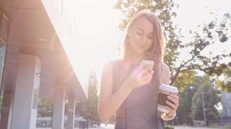 smartfon : Attractive business woman walking in the city, drinking coffee and using a smartphone in the morning. Steadicam stabilized shot in Slow motion. Lens flare. Wideo