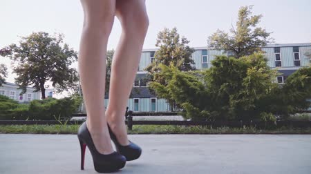 sapato : Sexy woman legs in black high heels shoes walking in the city urban street. Steadicam stabilized shot, Slow motion. Female legs in high-heeled shoes in the morning. Cinematic shot.