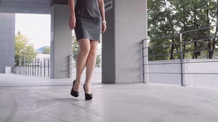 vysoký : Sexy woman legs in black high heels shoes walking in the city urban street. Steadicam stabilized shot, Slow motion. Female legs in high-heeled shoes in the morning. Cinematic shot.