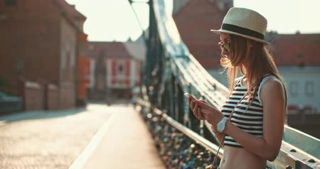 hipster : Woman using smartphone in the European city. Slow Motion, 4K. Hipster girl browsing Internet on a phone, texting and communicating, standing outdoors on the bridge. Travel.